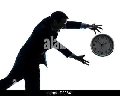 one  businessman running after time in silhouette studio isolated on white background - Stock Photo