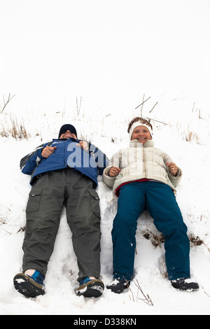 Happy middle aged couple relaxing on snow during winter vacation. - Stock Photo