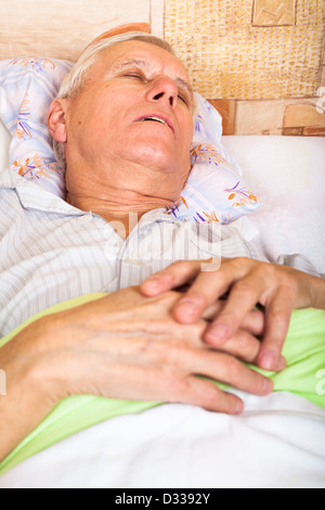 Close up of senior man sleeping in bed. - Stock Photo