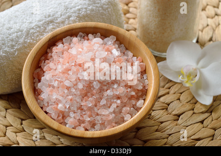 Pink salt from the Himalaya. Closeup of pink SPA salt in wooden bowl with orchid flower and towel. - Stock Photo