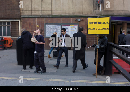 In Liverpool Street, London a man holds a sign promoting cookery lessons that leads to team building and teamwork. - Stock Photo