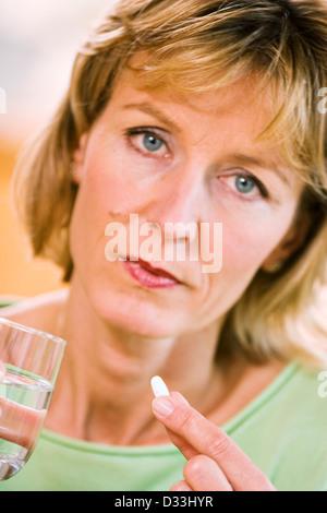Woman taking a pill - Stock Photo
