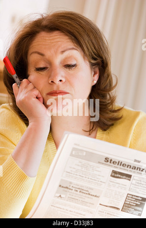 Woman reading vacancies in the newspaper - Stock Photo