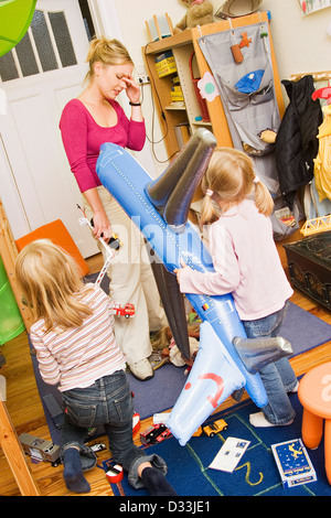 Mother and two children in an untidy child's room - Stock Photo