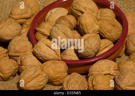 Walnuts in a ceramic bowl on burlap - Stock Photo