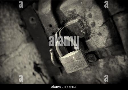 A brass padlock on an old wooden door in Perpignan, France. - Stock Photo