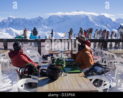 People skiers sitting outside Les Grandes Platieres mountain restaurant in Le Grand Massif ski area with view to - Stock Photo