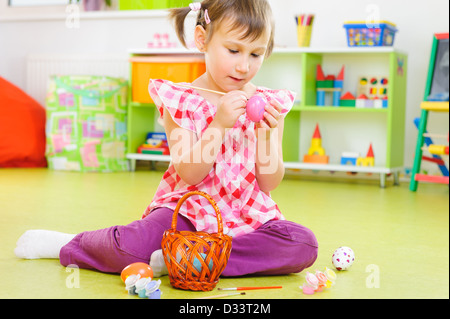 Little girl painting eggs for Easter holidays at home - Stock Photo