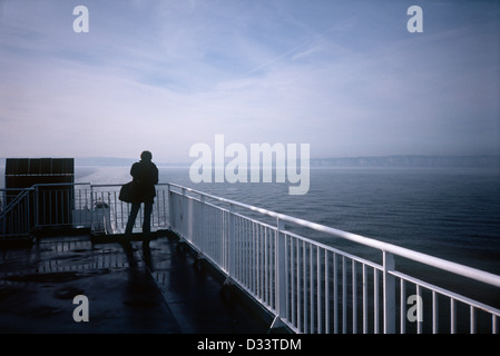 Passenger on ship at sea, distant cliffs - Stock Photo