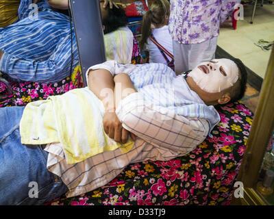 Feb. 2, 2013 - Phnom Penh, Cambodia - A man gets a facial at a beauty parlor in a market in Phnom Penh, Cambodia. - Stock Photo