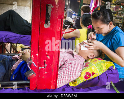 Feb. 2, 2013 - Phnom Penh, Cambodia - A man has his eyebrows tweezed at a beauty parlor in a market in Phnom Penh, - Stock Photo