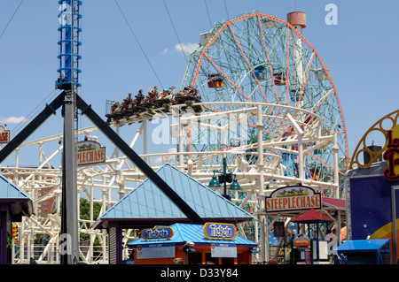 People enjoy the exuberance of the thrill of the fun fair rides at Coney Island, New York City. - Stock Photo