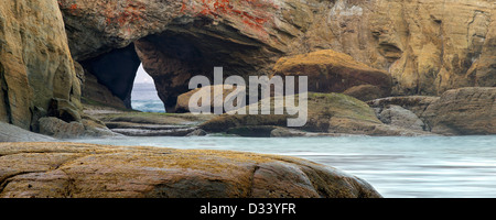 Beach with arch and light of boat in arch at Devil's Punchbowl State Natural Area. Oregon - Stock Photo