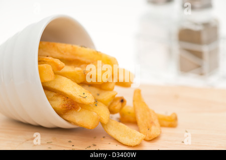 French fries falling out of a white bowl - shallow depth of field - Stock Photo