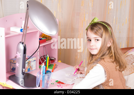 Cute little girl seated at her pink desk in her bedroom drawing and looking back over her shoulder at the camera - Stock Photo
