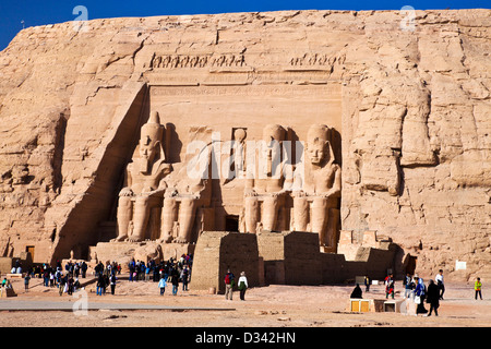 Tourists at the famous site of the Great Temple at Abu Simbel, Egypt are dwarfed by the huge statues of Ramesses - Stock Photo