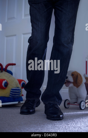 Male legs walking into a darkly lit child's bedroom with a door, toy car and toy dog in the background. - Stock Photo