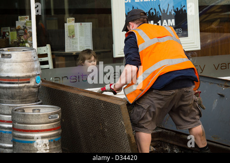A young child girl watching a man wearing orange hi-vis vest working delivering beer kegs to a pub, UK - Stock Photo