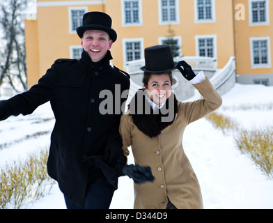 Young man and woman greeting happily coming guests - Stock Photo