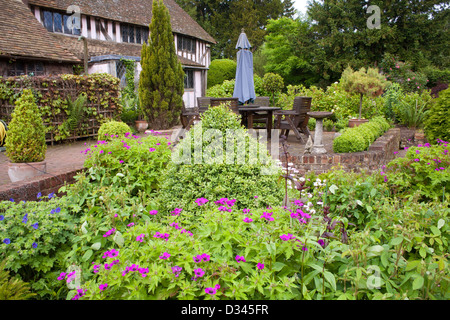 View across the borders towards the house with relaxing area on a patio. - Stock Photo