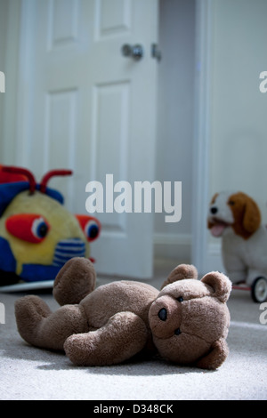 Brown Teddy Bear Laying On A Child S Bedroom Floor Stock
