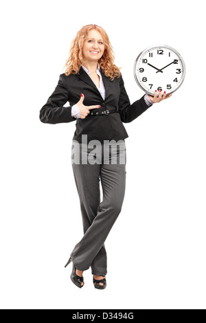 Full length portrait of a blond mature woman standing and pointing on a wall clock, isolated on white background - Stock Photo