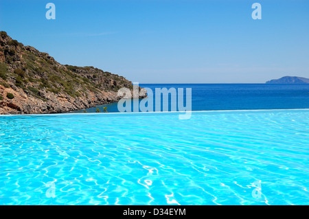 Infinity swimming pool with a view on Aegean Sea at the luxury hotel, Crete, Greece - Stock Photo