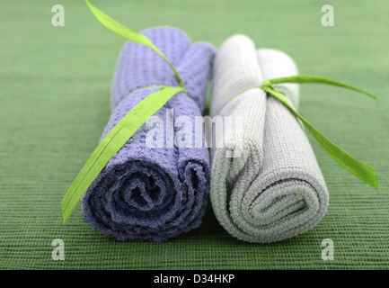 Purple and green wash cloths rolled up for bath at spa - Stock Photo