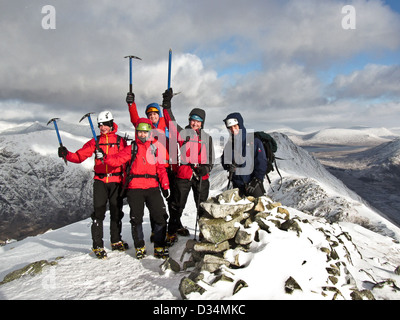 A group of winter mountaineers on the summit of Buachaille Etive Beag in Glencoe in Scottish highlands Scotland - Stock Photo