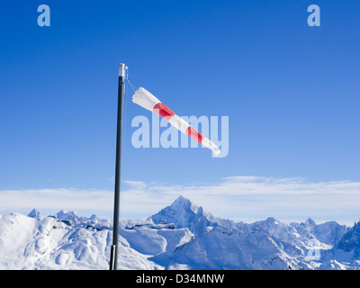 Windsock on a windy day at Les Grandes Platieres in Le Grand Massif with views to snowcapped mountains in French - Stock Photo