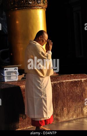 Buddhist Monk Praying at the Shwedagon Pagoda - Stock Photo