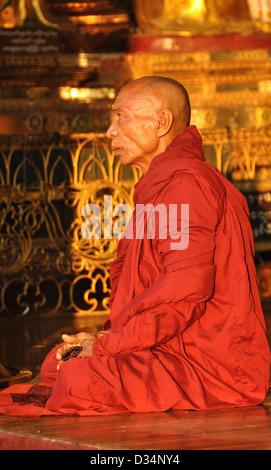 Buddhist Monk, at Dawn, Praying at the Shwedagon Pagoda - Stock Photo