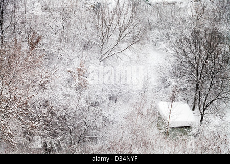 small snow-covered hut in winter forest - Stock Photo