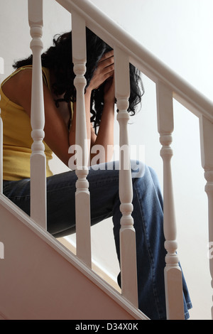 Despair. Female sitting side view on a step, head in hands. - Stock Photo