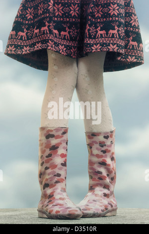 a girl in wellies on a table - Stock Photo