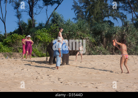 Tourists taking photographs on IPad on Mai Khao Beach Phuket Thailand - Stock Photo