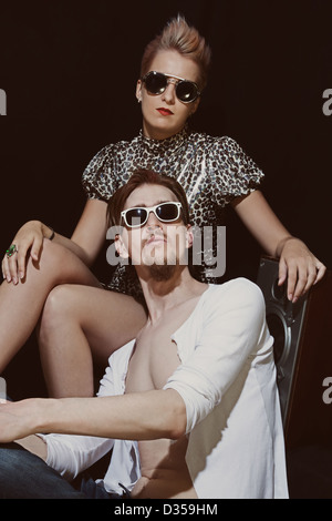 Studio portrait of young men and women wearing a stylish sunglasses on black background - Stock Photo