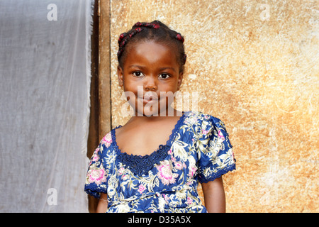 Portrait of a cute and sweet little black African girl, smiling but looking a bit shy, posing in front of her house. - Stock Photo