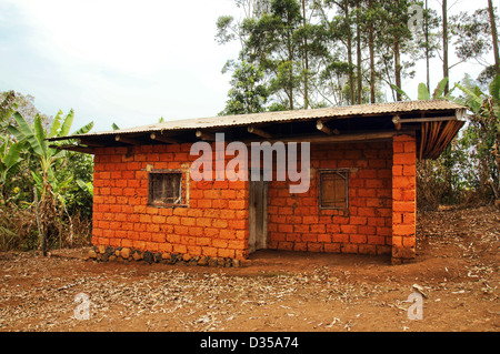 Typical red earth or soil brick with tin roof house for the workers and the like, in Africa. - Stock Photo
