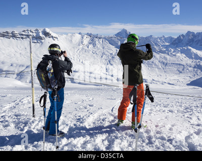 Skiers taking photos snowcapped mountains from Les Grandes Platieres in Le Grand Massif ski area in French Alps. - Stock Photo