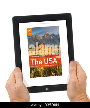 Reading a Rough Guide travel book with the Kindle app on an Apple iPad 4th genration retina display tablet computer - Stock Photo
