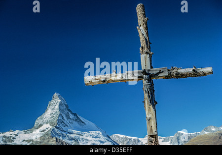 A rustic cross with a crucifix points to the famous Matterhorn mountain, one of the highest peaks in the Alps on - Stock Photo