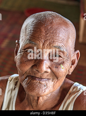 Elderly Buddhist priest sits on the floor of a temple outside Phnom Penh, Cambodia. - Stock Photo