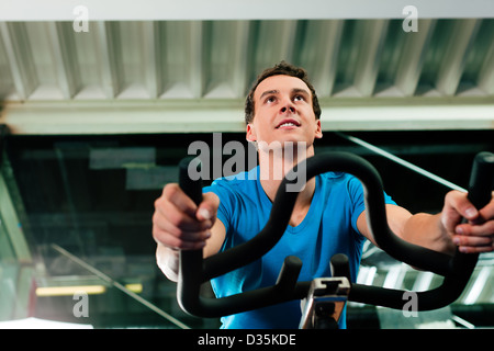 Man spinning in the gym, exercising his legs doing cardio training on bicycle - Stock Photo