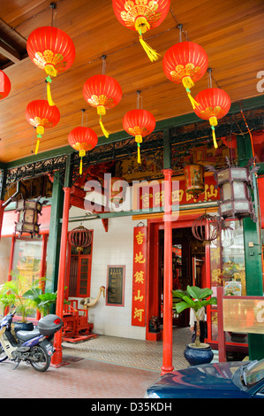 Chinese Taoist temple entrance, with colourful hanging lanterns and large amounts of red colour. - Stock Photo