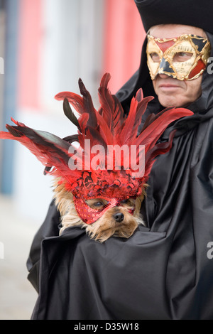 man in a venetian mask carrying a Yorkshire Terrier  dog in a mask for the Venice carnival - Stock Photo