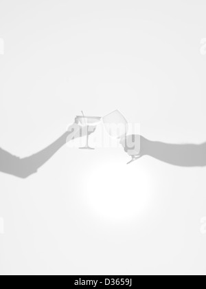 close-up of two hands silhouettes holding two different glasses, behind a diffuse surface, cheers  - Stock Photo