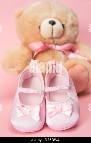 Pink baby booties and teddy bear - Stock Photo
