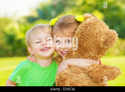 Photo two cute child hugging outdoors, brother and sister having fun on backyard in spring, nice little girl with - Stock Photo