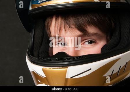 Child Wearing A Motorsport Crash Helmet - Stock Photo